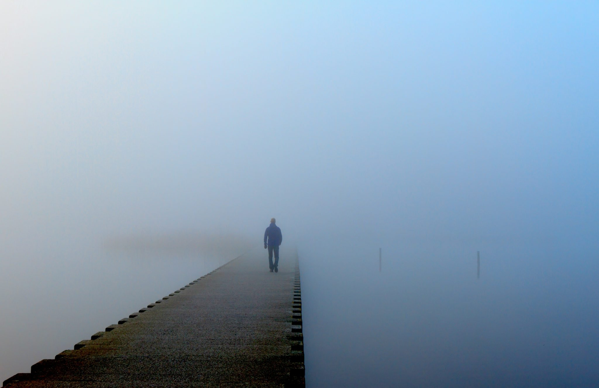 Man walking on dock with thick fog around him