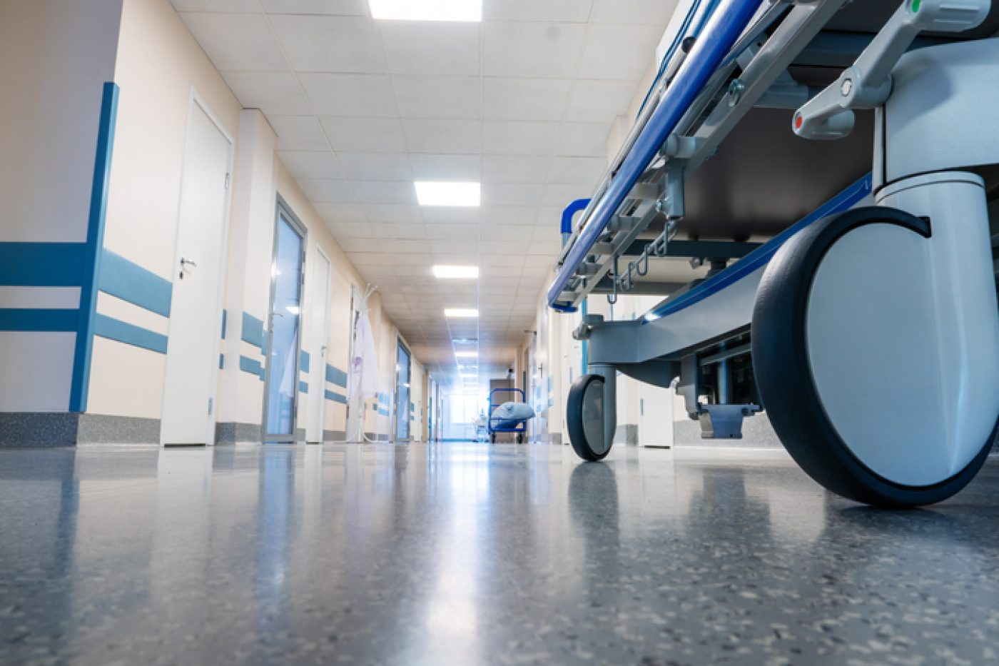 View from ground floor up. Hospital bed on wheels in corridor. h